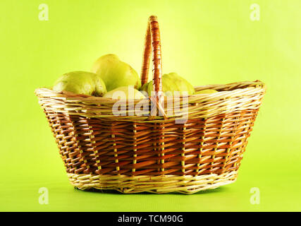 sweet quinces in basket, on green background - Stock Photo