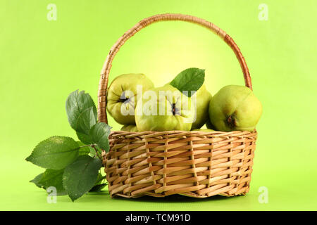sweet quinces with leaves in basket, on green background - Stock Photo