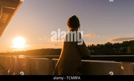 Woman admiring sunset from deck of cruise ship - Stock Photo