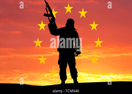 Silhouette of military soldier, shot, holding gun, colorful sky, Concept of a terrorist. Silhouette terrorists with rifle, national flag on background - Stock Photo