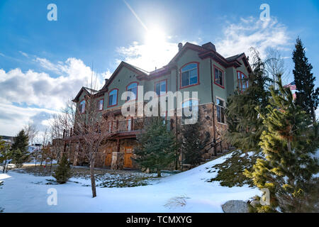 Facade of a home surrounded with lush trees and snowy ground in winter - Stock Photo