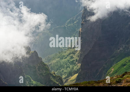 View down from mountain peak at a valley in distant. Pico do Arieiro on Portuguese island of Madeira - Stock Photo