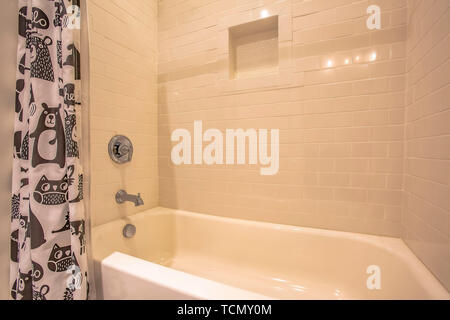 Bathtub and shower inside a bathroom with glossy white wall - Stock Photo