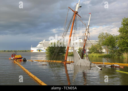 Stadersand, Germany. 08th June, 2019. The sunken historical sailing ship 'No 5 Elbe' is almost completely under water in the harbour of Stadersand, in the background the cruise ship Aida Perla is sailing on the Elbe. The historical sailing ship, which has only recently been extensively renovated, collided with a container ship on the Elbe and sank. Five people were injured in the accident in Stade on Saturday, one of them a woman, according to the Hamburg police. Credit: Bodo Marks/dpa/Alamy Live News - Stock Photo