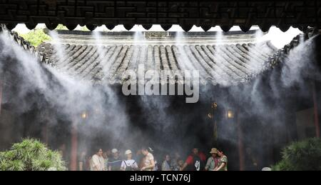 Suzhou, China's Jiangsu Province. 9th June, 2019. Tourists walk under mist at the Lingering Garden, one of the most famous Chinese classical gardens, in Suzhou, east China's Jiangsu Province, June 9, 2019. The classical garden in Suzhou has opened its intelligent spraying system to cool tourists in hot summer. Credit: Hang Xingwei/Xinhua/Alamy Live News - Stock Photo