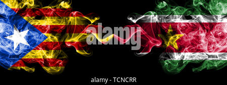 Catalonia vs Suriname, Surinamese smoke flags placed side by side. Thick colored silky smoke flags of Catalonia and Suriname, Surinamese - Stock Photo