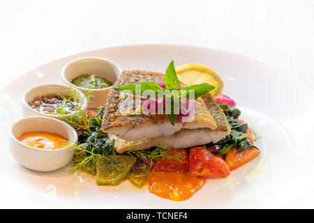 close up of grilled pan seared sea bass snapper fillet with vegetable and italian sauces , spicy, mayo,pesto, olives isolated on white plate natural b - Stock Photo
