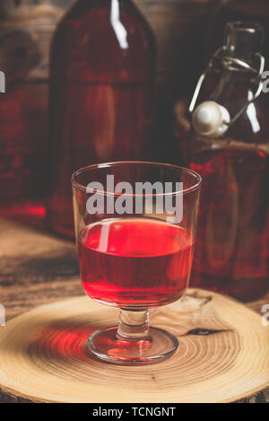 Homemade red currant wine in drinking glass - Stock Photo