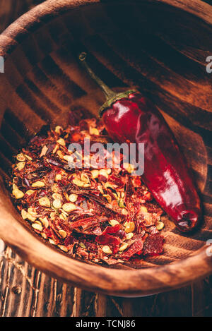 Flakes of ground red chili pepper in wooden bowl - Stock Photo