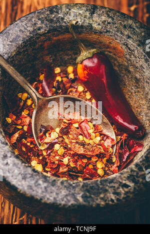 Red chili pepper grinded in mortar. High angle view - Stock Photo