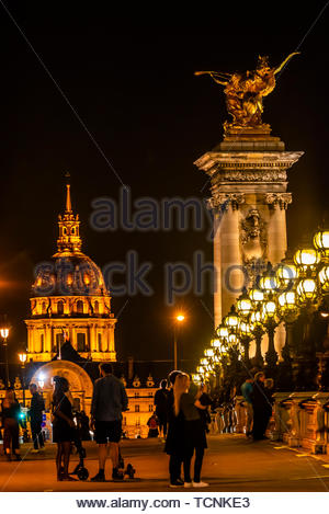 Pont Alexandre III (bridge) across the Seine River with Hotel des Invalides behind. The bridge is the most ornate in the city and features art nouveau - Stock Photo