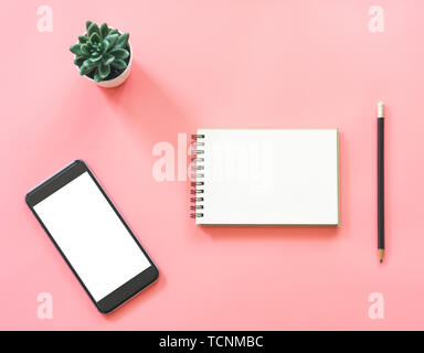 Flat lay mockup design of workspace desk with blank notebook, smartphone, coffee, stationery on pink pastel color with copy space - Stock Photo