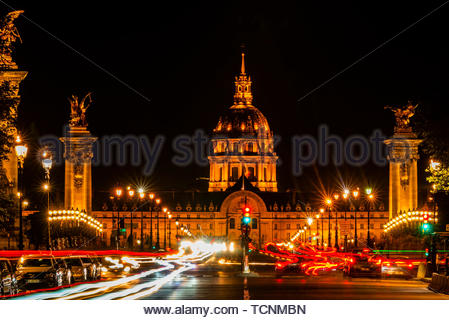 Blurred traffic, Pont Alexandre III (bridge) across the Seine River with Hotel des Invalides behind. The bridge is the most ornate in the city and fea - Stock Photo