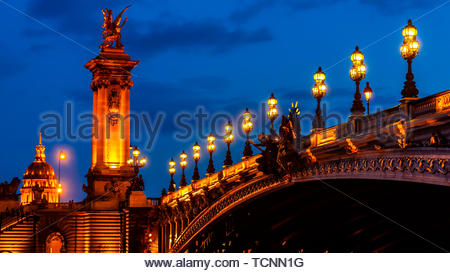 The ornate Pont Alexandre III (bridge) across the River Seine with its gilded sculptures featured winged horses behind and Hotel des Invalides in back - Stock Photo