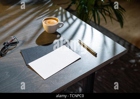Close up of white coffee cup, blank envelopes and glasses and pen on dark wooden table with tropic plant on background. - Stock Photo