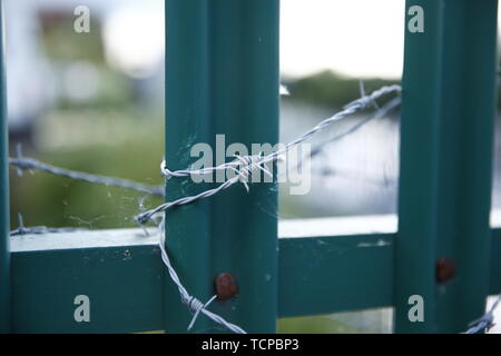 Barbed wire around a green metal fence. - Stock Photo