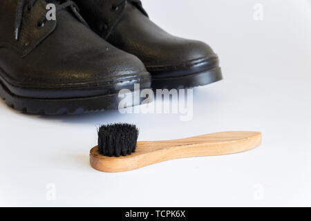 Black shoes and Shoe brush on white background. Shoe care with a brush. Shoe brush. No people. - Stock Photo