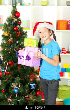Little girl holding gift boxes near christmas tree - Stock Photo