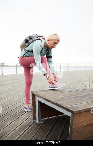 Blonde active female in sportswear tying shoelace on sports-shoe while bending over wooden bench before outdoor training - Stock Photo