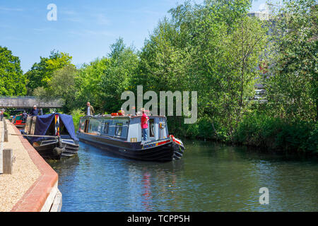 Narrowboat sailing on the Basingstoke Canal passing through Woking town centre by the Saturn Trail, Surrey, southeast England on a sunny day - Stock Photo