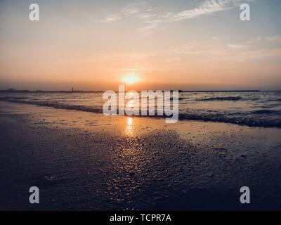 The setting sun, low tide and high tide on the sea have different scenery, and the setting sun falls and reflects on the sea. - Stock Photo