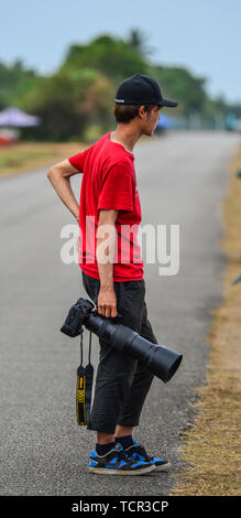 Langkawi, Malaysia - Mar 31, 2019. A young man with professional camera (Nikon DSLR and tele lens) standing at the national park on Langkawi Island. - Stock Photo