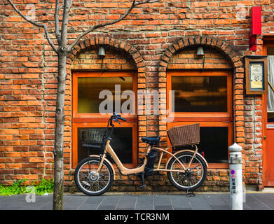 Tokyo, Japan - Apr 9, 2019. A bicycle at the old brick house in Tokyo, Japan. - Stock Photo