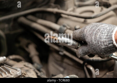 A serviceman repairs a car while replacing the spark plugs while holding one of them in hand with a glove while unscrewing them from the engine with t - Stock Photo