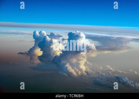 Dramatic Cumulonimbus cloud formations at sunset taken from an aircraft window over southern europe. - Stock Photo