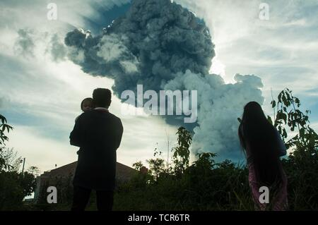 Sumatra, Indonesia. 09th June, 2019. The eruption of Mt. Sinabung, North Sumatra on June 9, 2019 at 16:28 with the ash column height observed ± 7,000 m above the peak (± 9,460 m above sea level). The ash column was observed to be black with thick intensity leaning southward. Seen from kabanjahe city. 'There was a hot cloud in the 3.5 km southeast and 3 km south and a roar came to the volcano observation post of Sinabung Currently Mount Sinabung is in Status * Level III (Standby)' Said vulcano officer guard from radio communication. Credit: Sabirin Manurung/Pacific Press/Alamy Live News Credit: - Stock Photo