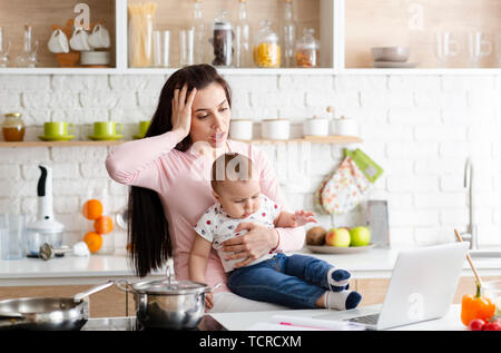 Desperate mother looking at laptop, working with baby in kitchen at home - Stock Photo
