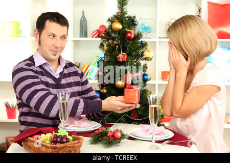 Young happy couple with presents sitting   at table near Christmas tree - Stock Photo