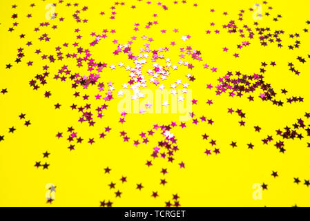 Bright pink stars on bright yellow background. Trendy colours of summer 2019. - Stock Photo
