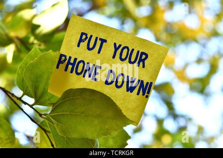 Word writing text Put Your Phone Down. Business photo showcasing end telephone connection saying goodbye caller Piece of square paper use to give nota - Stock Photo