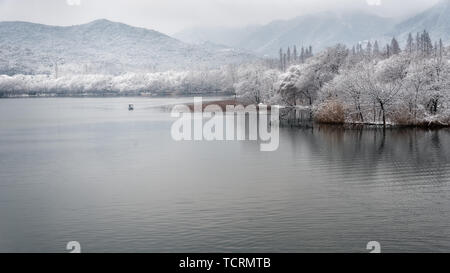 After the heavy snow in Hangzhou, a lone boat sailed in the heart of the lake. Unlike the hustle and bustle of the West Lake next door, Maojiabu found a quiet on the shores of Xizi Lake. - Stock Photo