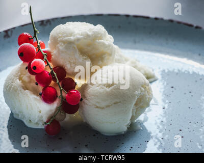 Bright, flavor ice cream and a sprig of red currants. Isolated background. Close-up, top view. Concept of tasty and healthy food - Stock Photo
