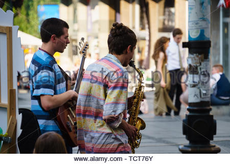 Street performance in center of Belgrade, couple of young enthusiastic musicians playing jazz for the crowd - Stock Photo