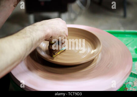 a master ceramist with 13 years of experience makes plate from red clay on a potter's wheel, on a sheet of particle board for better removal and furth - Stock Photo