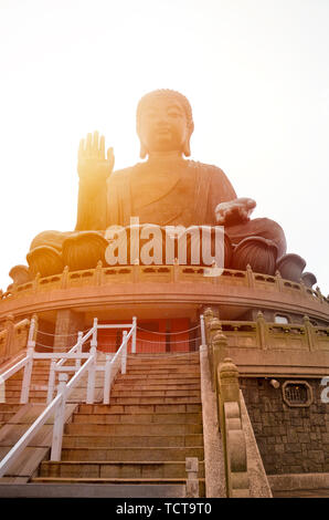 The enormous Tian Tan Buddha at Po Lin Monastery in Lantau Island, Hong Kong. Photographed during sunset with orange sun shining behind the statue. Popular tourist attraction. - Stock Photo