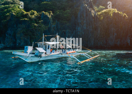 Banca local boat on turquoise water against huge limestone cliffs. Island hopping tour trip. Exploring Philippines summer vacation journey holidays - Stock Photo
