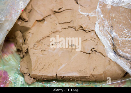 ceramic meeting for the exchange of experience. reportage. familiarity with different types of clay. Piece is cut off from the briquette for to do the - Stock Photo