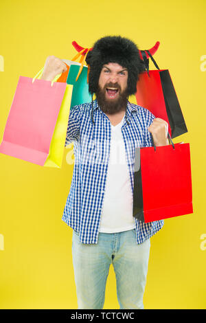 Shopping champion. Happy hipster in bull horns hat holding paperbags after successful shopping. Bearded man smiling with shopping bags. Shopping is his addiction - Stock Photo