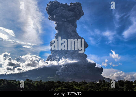 Karo, North Sumatra, Indonesia. 09th June, 2019. Mount Sinabung during the eruption seen from Beganding Villages in Karo, North Sumatra. Sinabung spewed 7000 meters of volcanic ash in the sky, which has rumbled since 2010 and witnessed deadly eruptions spewing thick fur after activity increased in recent days. Credit: Albert Ivan Damanik/ZUMA Wire/Alamy Live News - Stock Photo