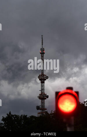10 June 2019, Bavaria, München-Freimann: Dark clouds pass over the transmission tower of the Bayerischer Rundfunk in Freimann. After heavy rain, the state capital is now rain-free again. Photo: Felix Hörhager/dpa - Stock Photo