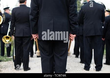 A closeup of the hands of a drummer at a parade. Ensemble in white shirts. white sticks. The concept of a military parade and march. - Stock Photo