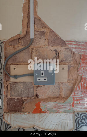 The exposed plastering showing exposed brick work and an electrical outlet and the wiring in the wall, in need of repair, nobody in the image - Stock Photo
