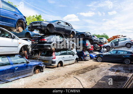 Cars with their wheels removed are stacked in piles of 3 cars with paths between them in a breakers scrap yard - Stock Photo