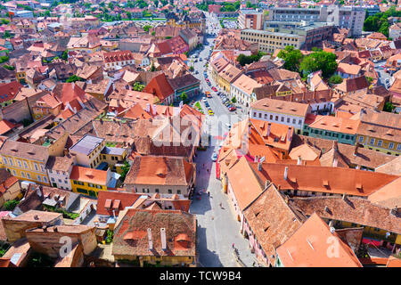 Aerial view of Sibiu traditional houses with brown-orange roofs and a street in the middle, near the city pedestrian area/center. View from the watch  - Stock Photo
