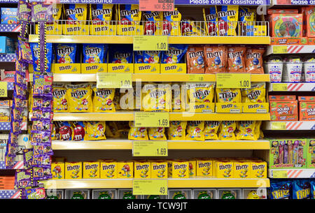 Multiple shelves full of a variety of sweets on display in store. B&M discount store, UK - Stock Photo