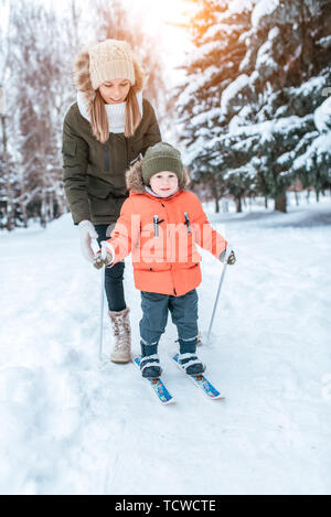 Young mother insures supports child children's skis, little boy son of 3 years. Winter forest park, background snow drifts trees. Concept taking care  - Stock Photo